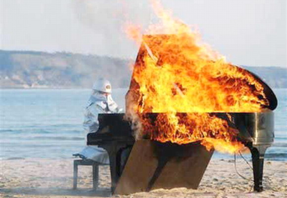 This piano is blazing! Famous Japanese pianist Yosuke Yamashita, in fireproof gear, plays the piano for 10 minutes in this firey performance peice!